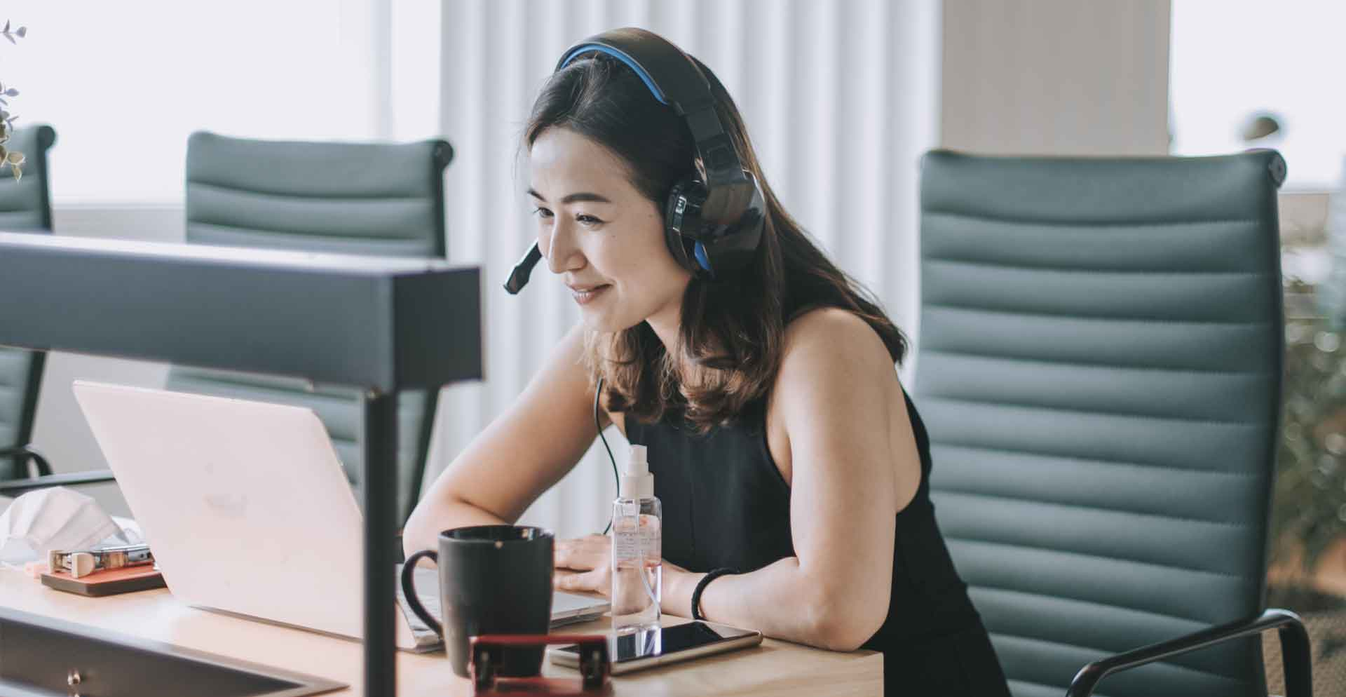 woman_watching_webinar_on_laptop_smiling_flipped_cropped