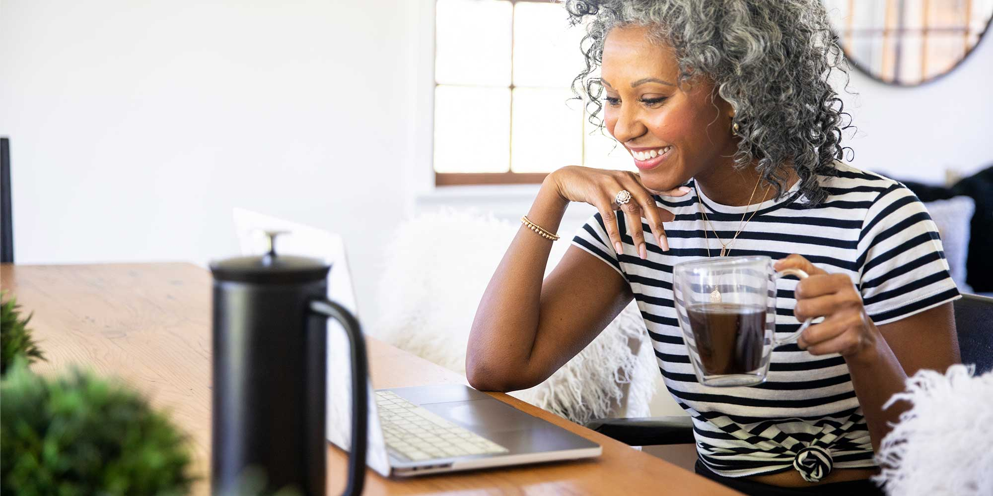woman_looking_at_laptop_with_coffee