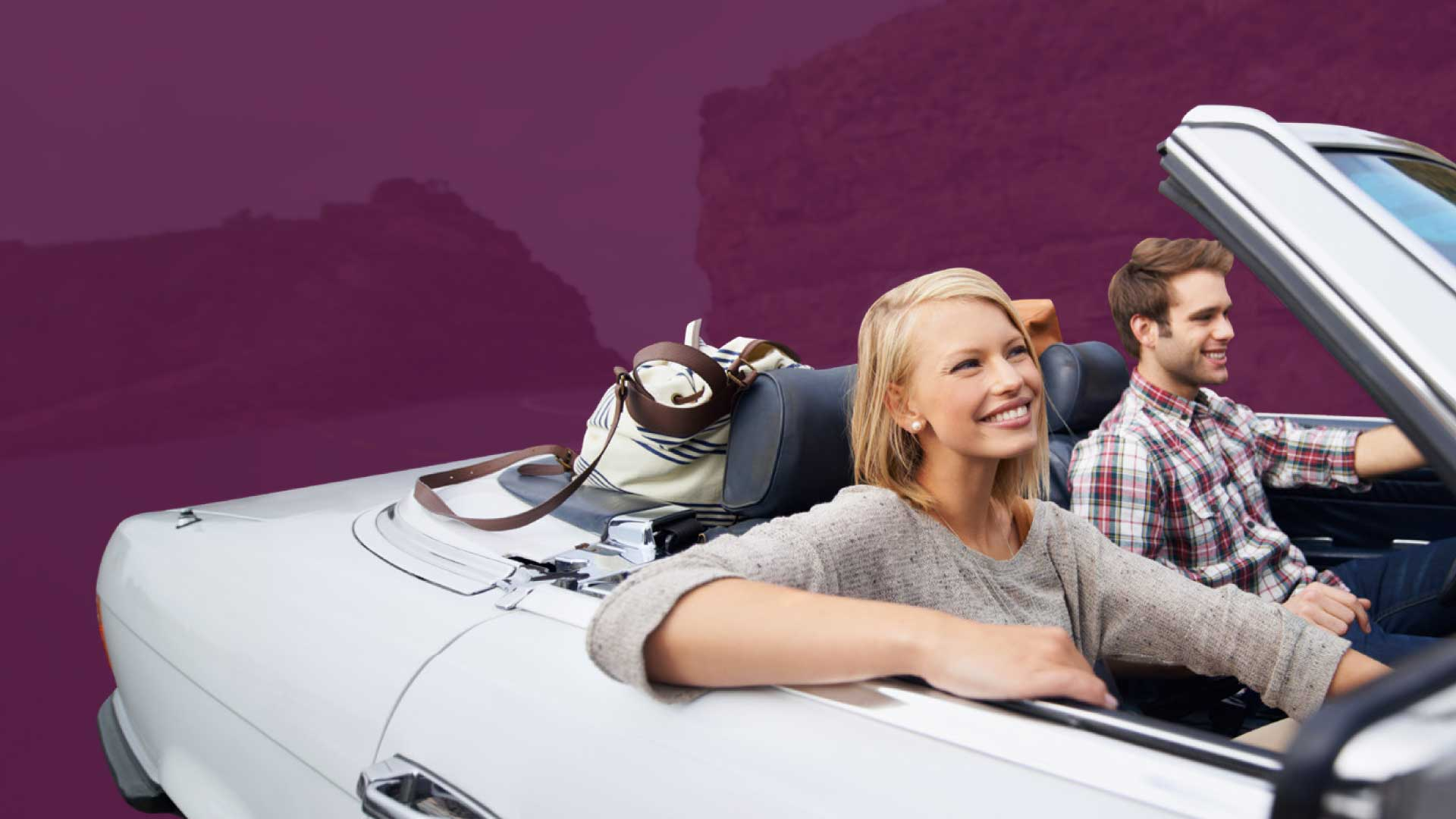 young_couple_riding_in_convertible_car_smiling