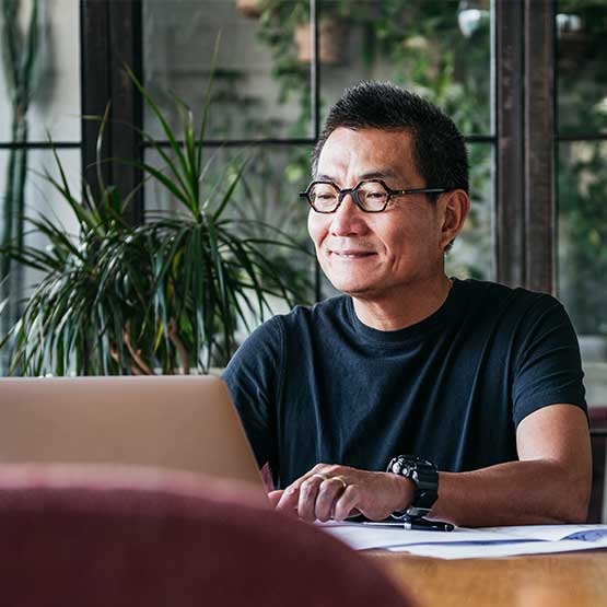 smiling_chinese_man_looking_at_laptop